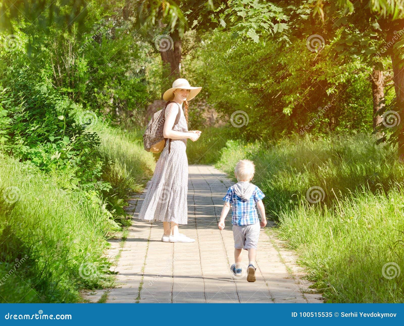 走沿路的妈妈和儿子在公园 回到视图 垂直的框架