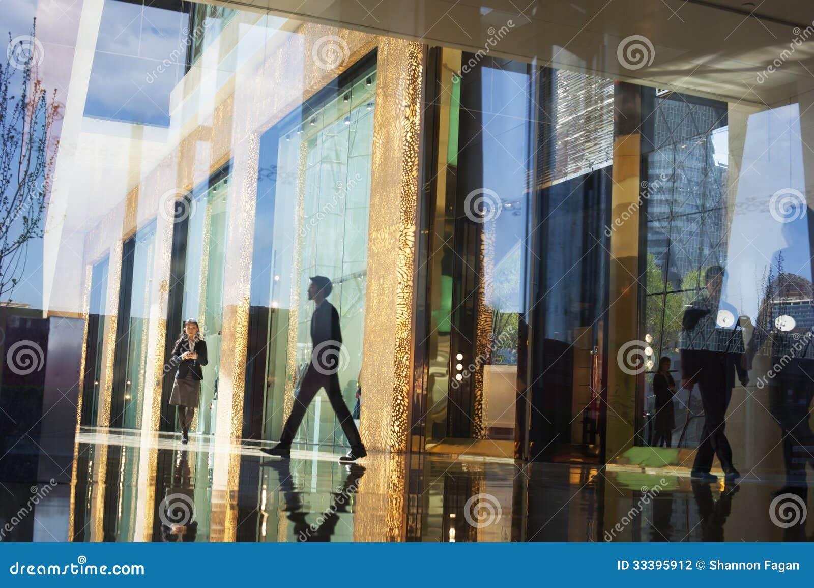 走通过一座办公楼的大厅的商人在玻璃墙的另一边的