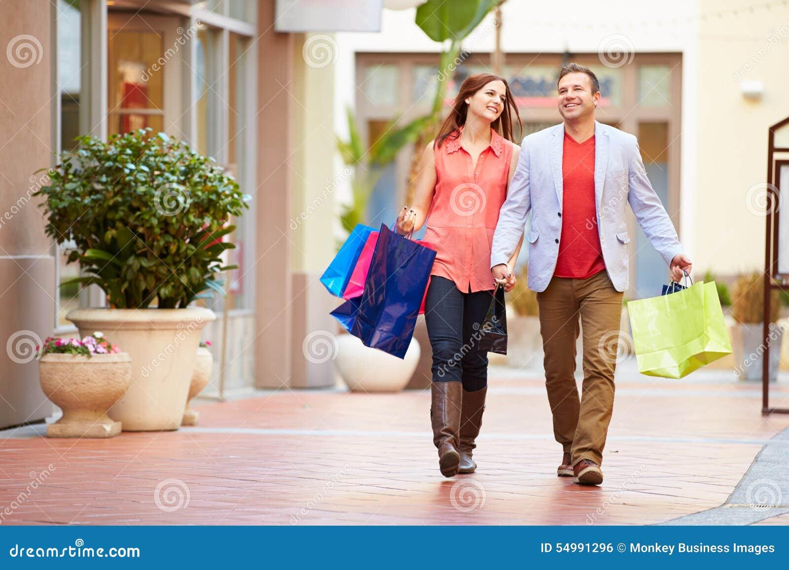 走通过与购物袋的购物中心的年轻夫妇