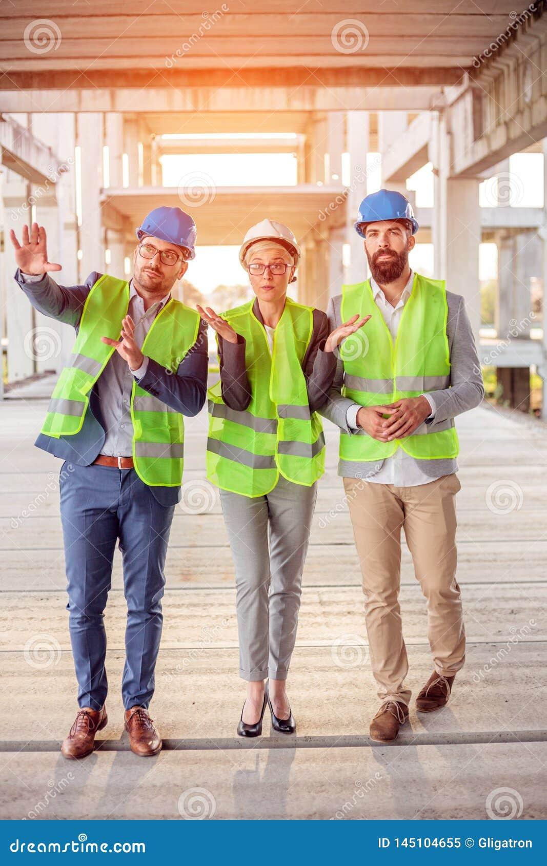 走通过预制的具体工地工作的混合群建筑师,检查工作进展