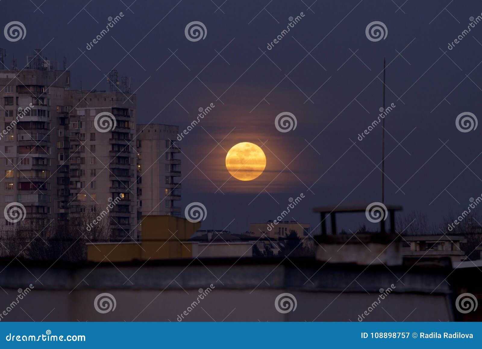 超级名门出身月亮2018年1月31日从Easterm欧洲,保加利亚,索非亚 在海运的蚀月球月亮 在大厦旁边的超级月亮
