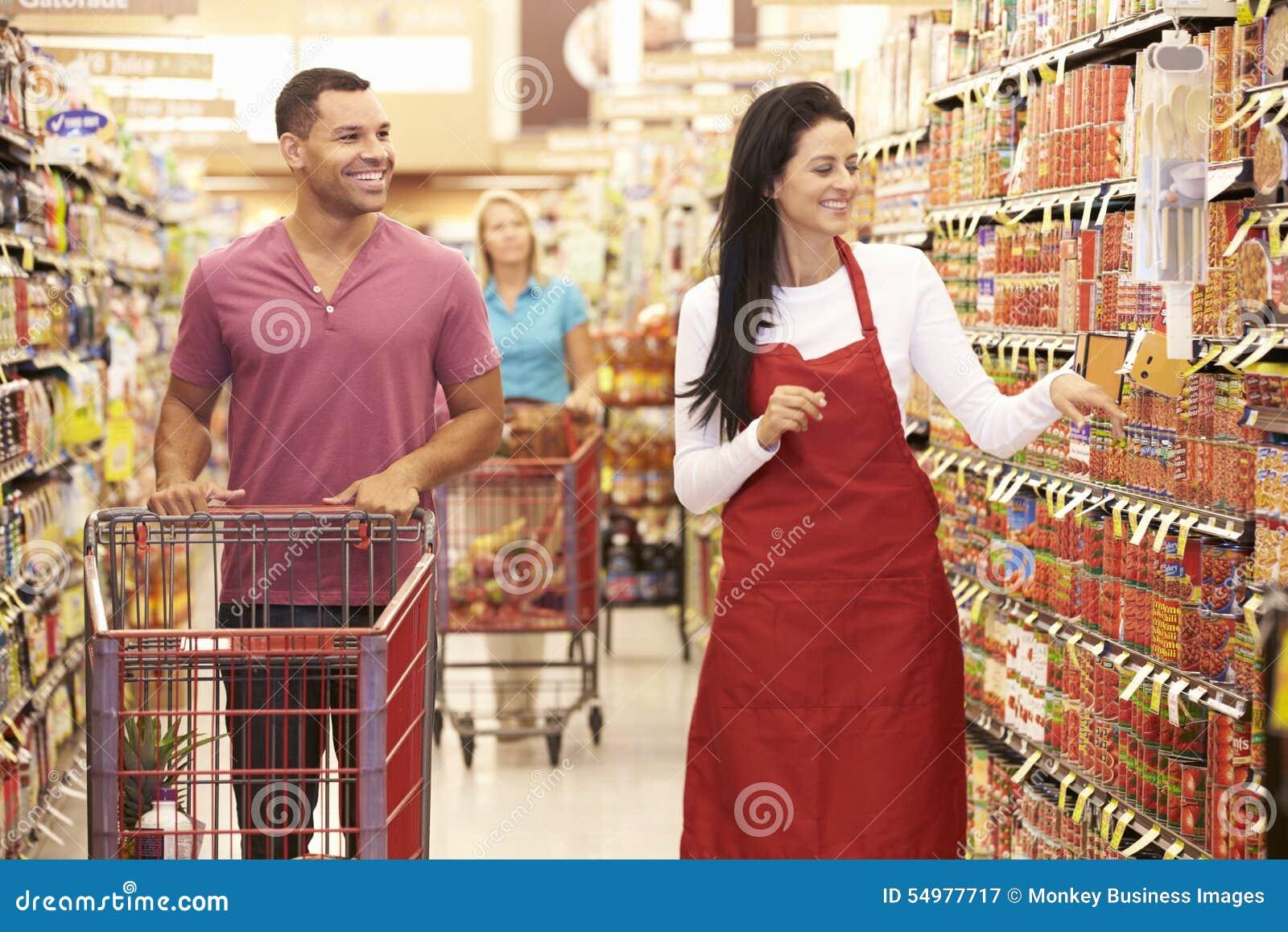 超级市场杂货走道的人有辅助的销售的