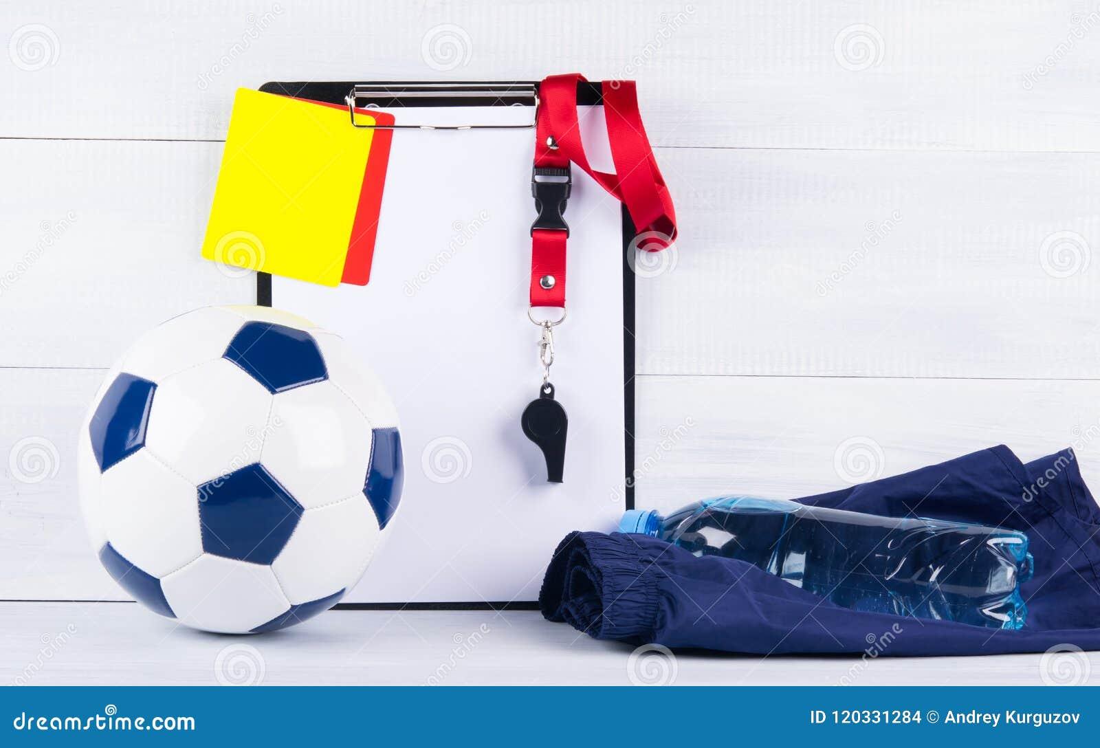 足球、一个瓶在体育短裤的水和一声口哨、惩罚卡片和一种片剂记录的法官, backgr