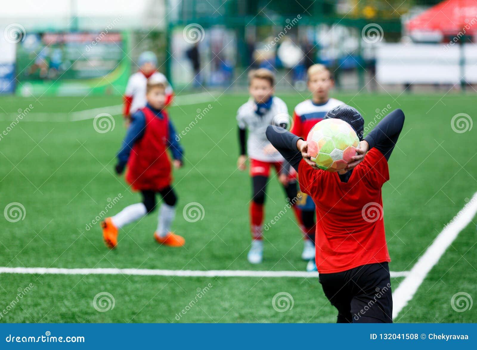 足球队-红色,蓝色,白色一致的戏剧足球的男孩在绿色领域 滴下的男孩 滴下的技能