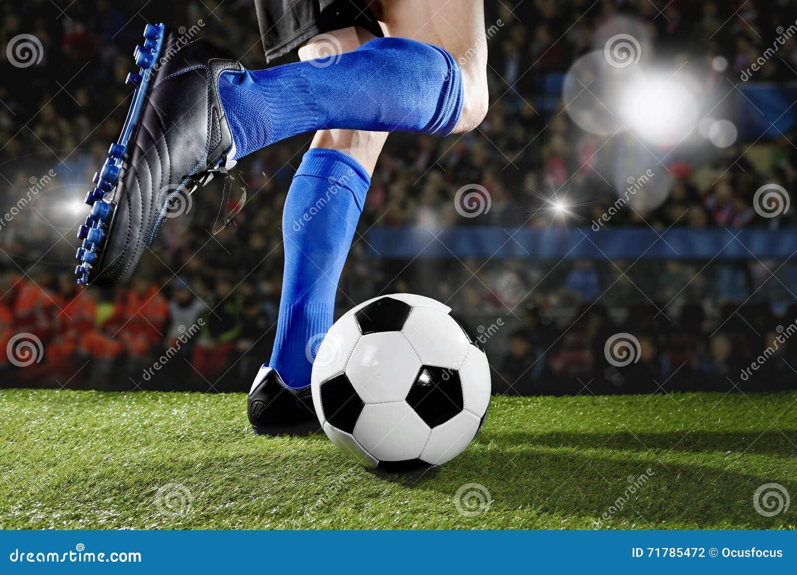 跑和滴下在足球场的行动的足球运动员参加比赛