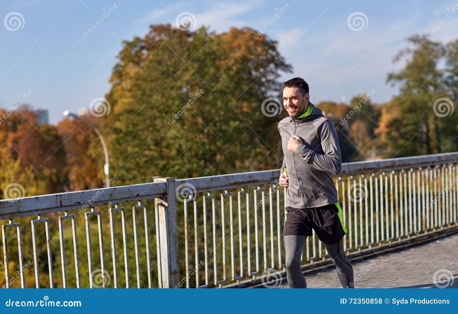 跑在城市桥梁的愉快的年轻人