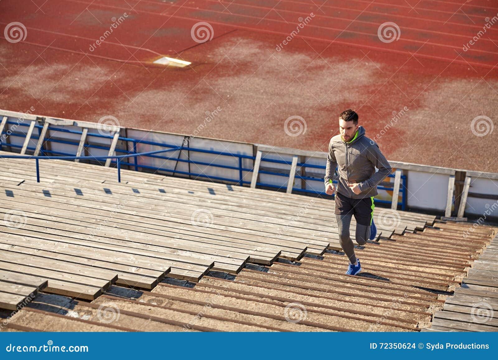 跑在楼上在体育场的愉快的年轻人