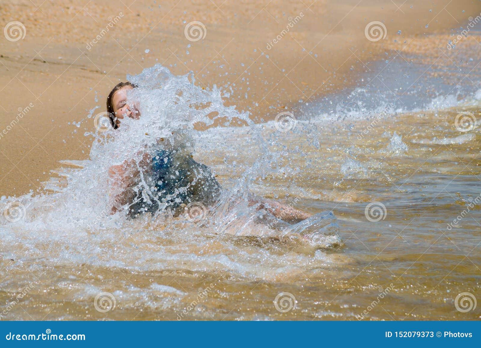 跑在波浪的愉快的孩子在海滩的暑假时在海洋学会海岸的女孩游泳