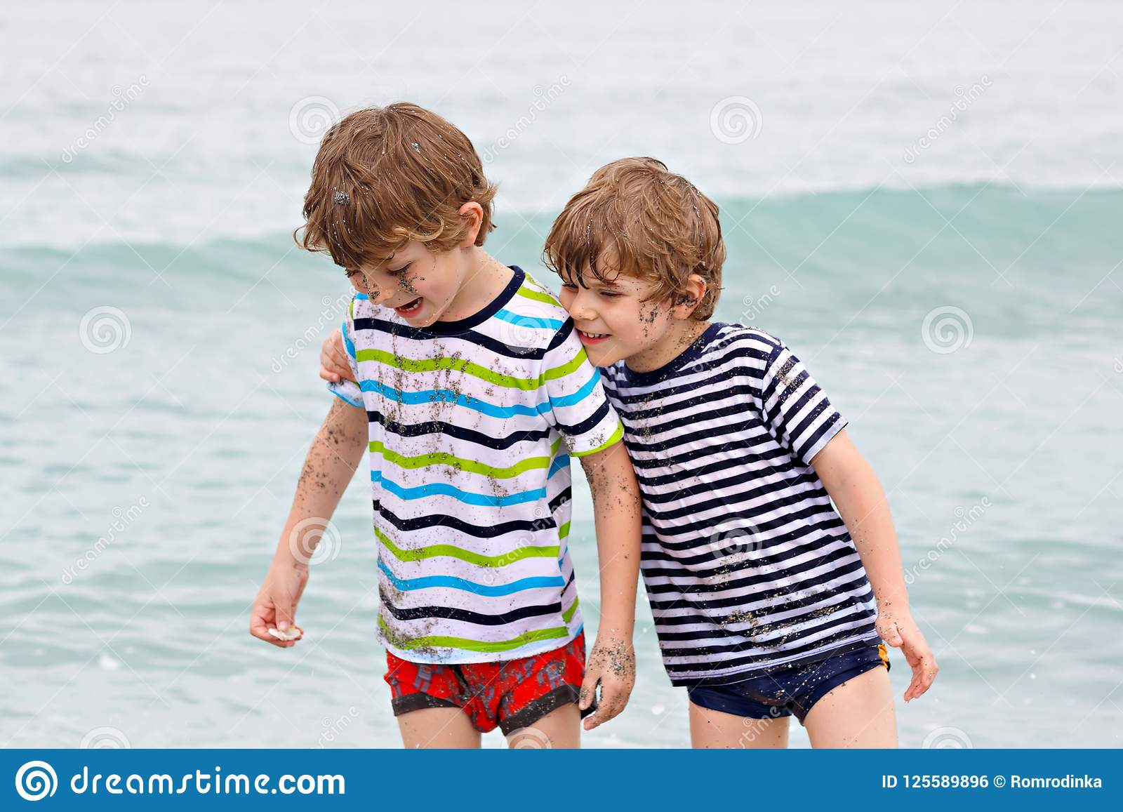 跑在海滩的两个愉快的小孩男孩海洋 滑稽儿童、兄弟姐妹、孪生和最好的朋友做
