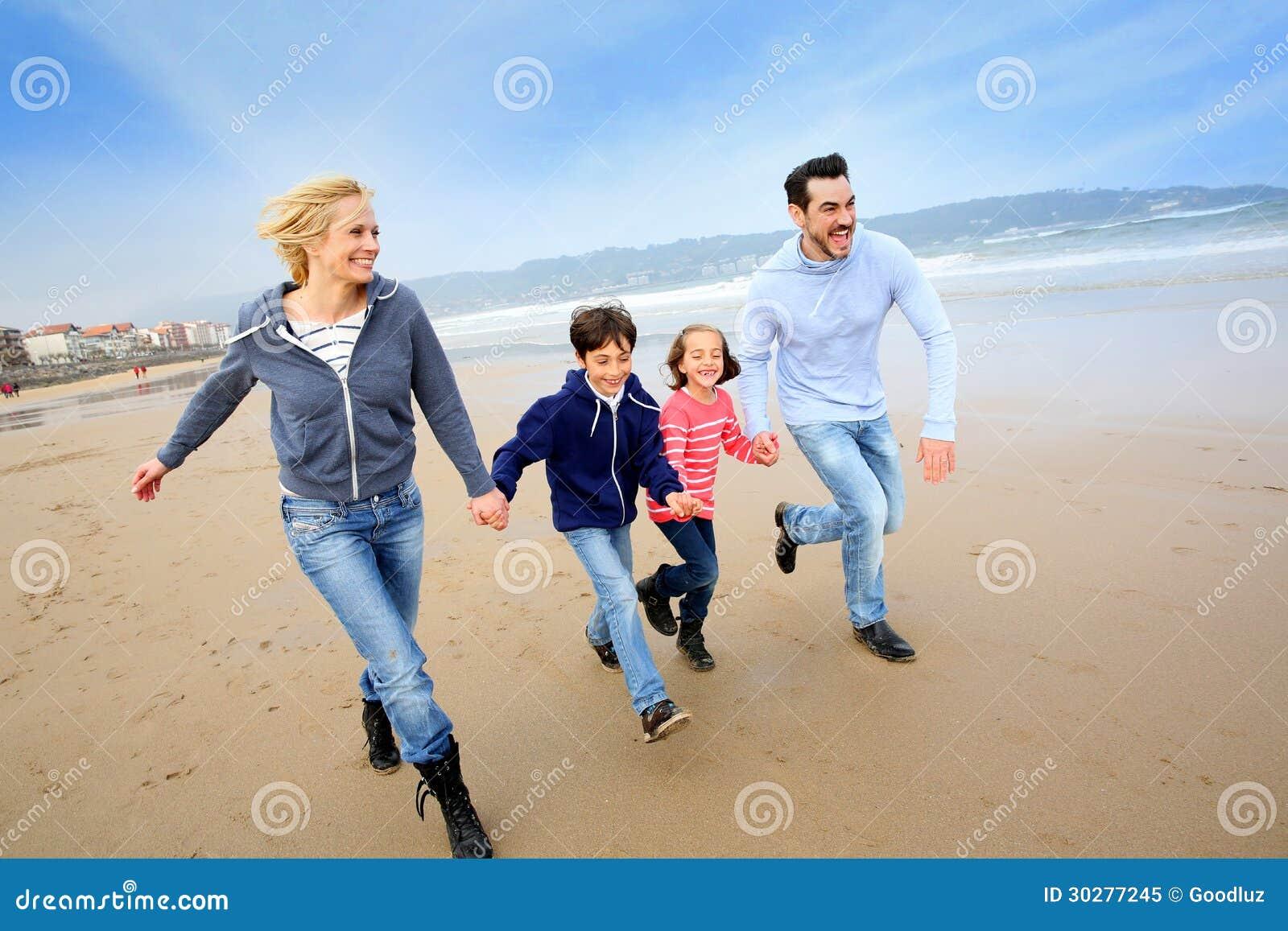 跑在海滩的家庭