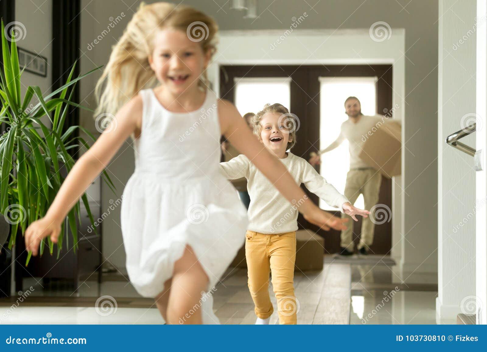 跑在照相机,家庭的激动的孩子移动在新房里