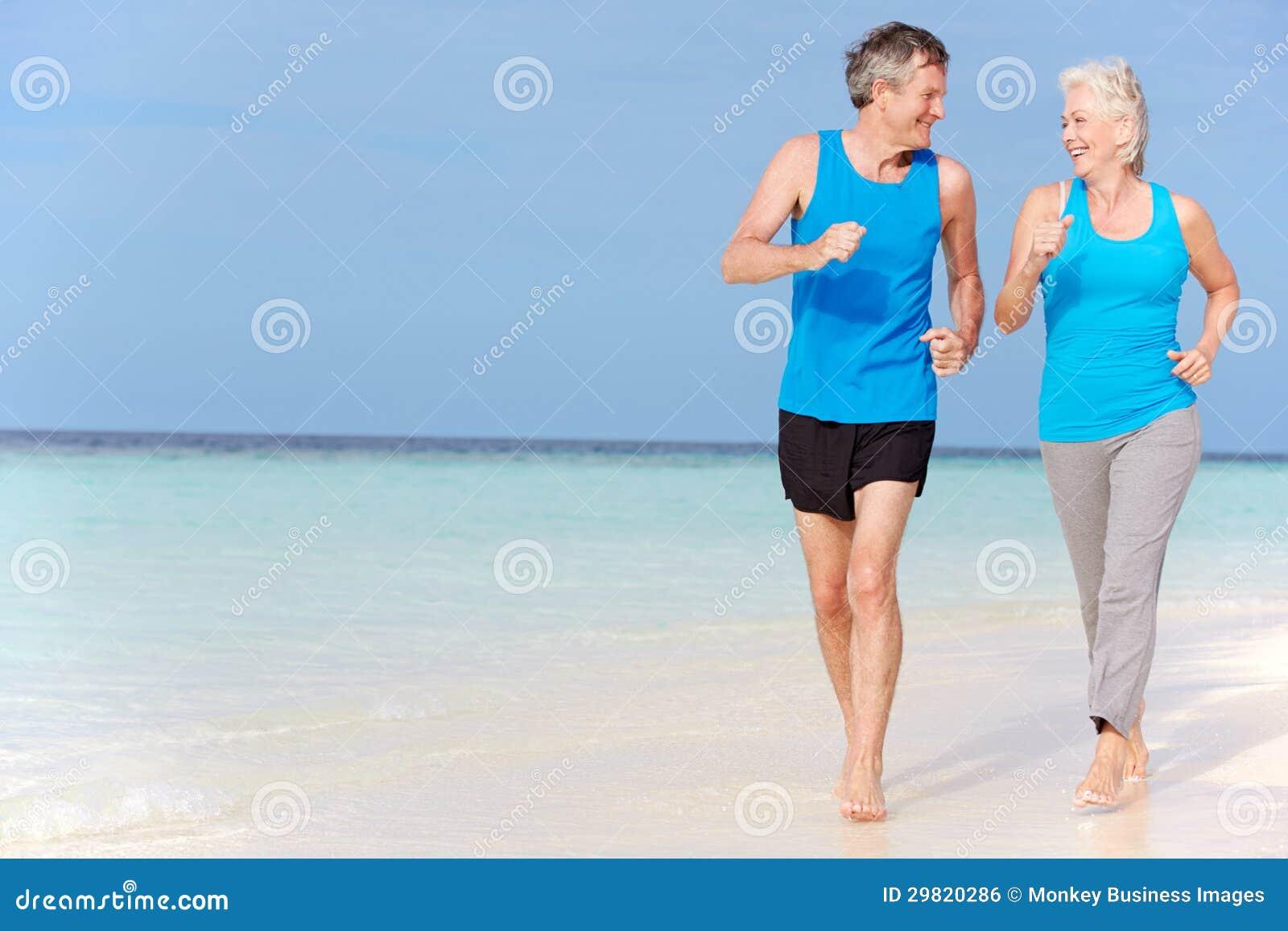 跑在美丽的海滩的资深夫妇