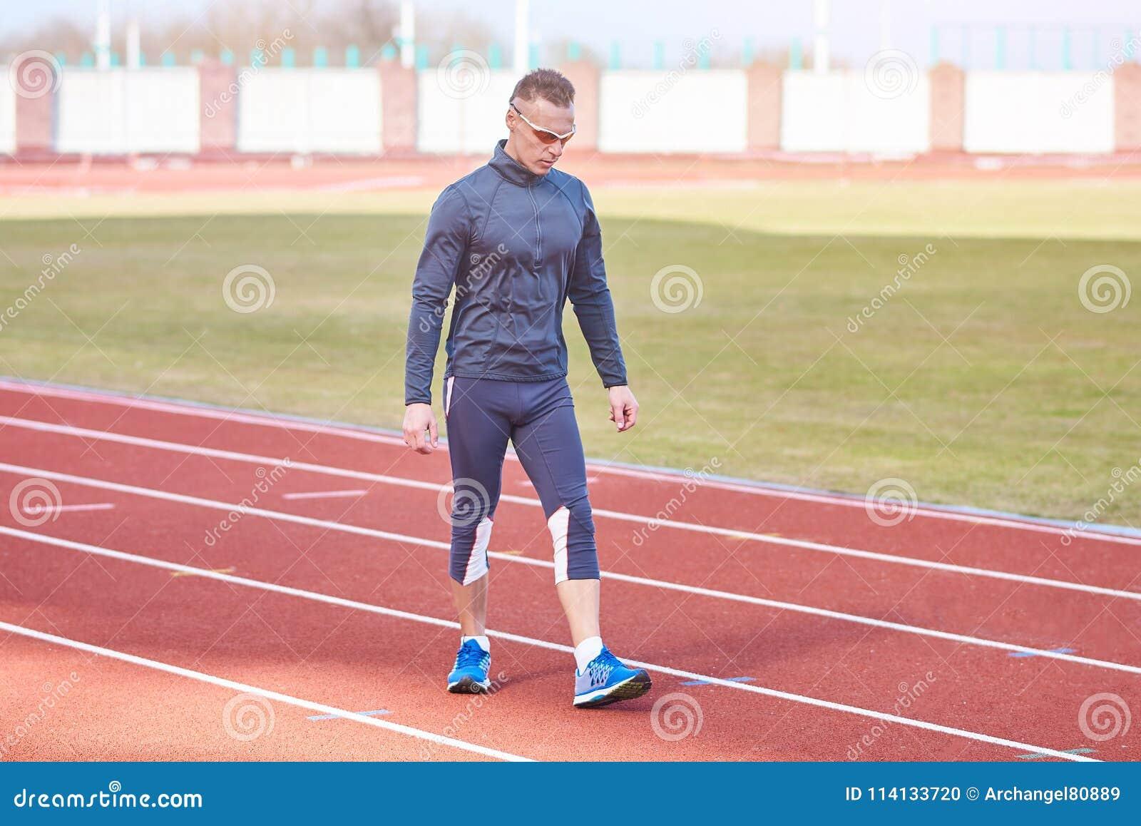 跑在踏车体育场的英俊的运动人