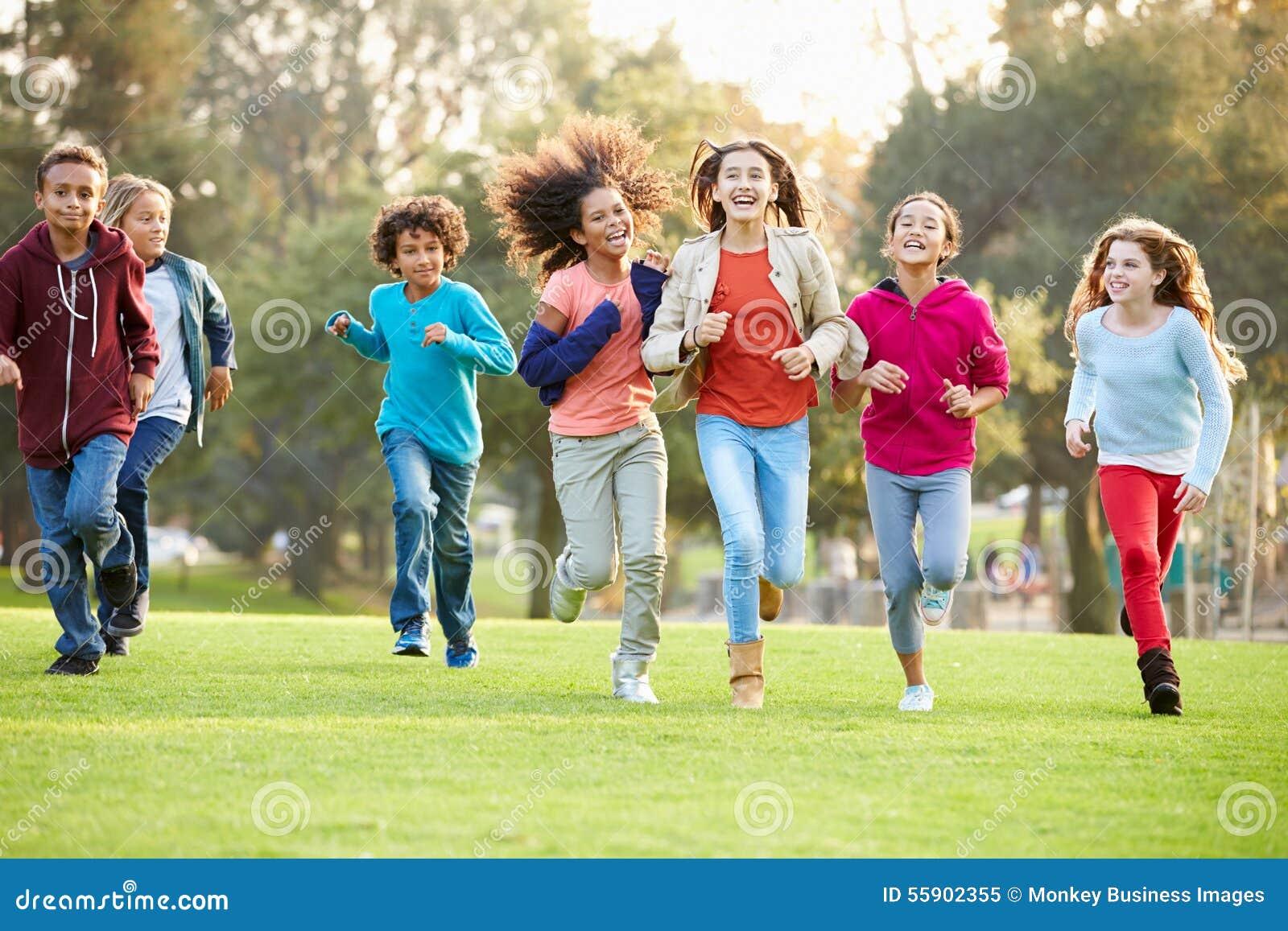 跑往照相机的小组幼儿在公园