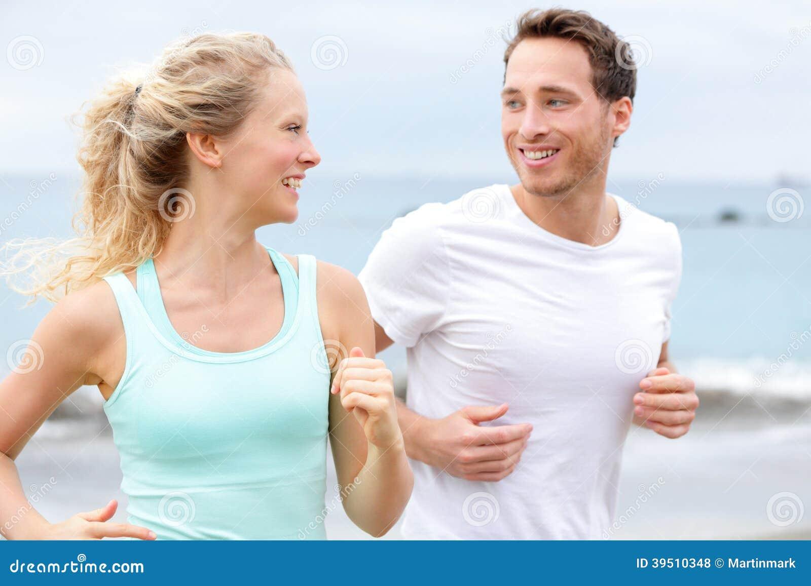 跑步在海滩谈话的锻炼连续夫妇