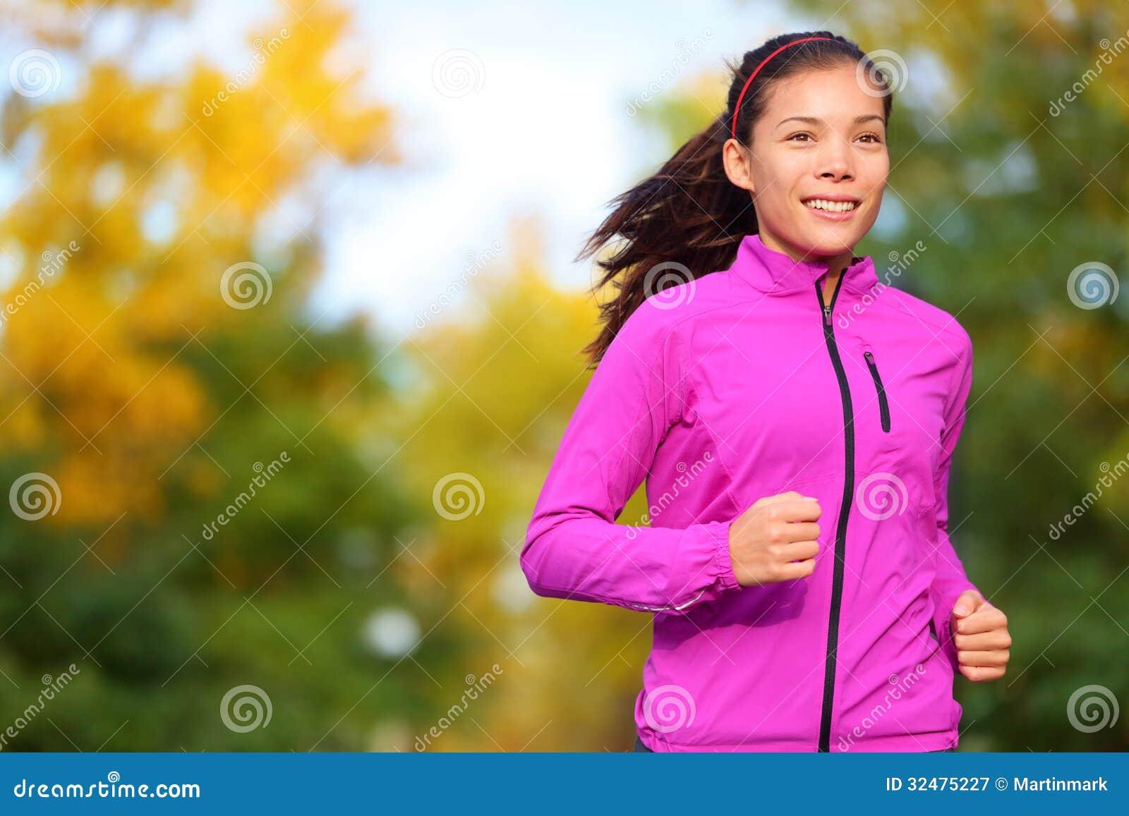 跑步在秋天的秋天森林里的连续妇女