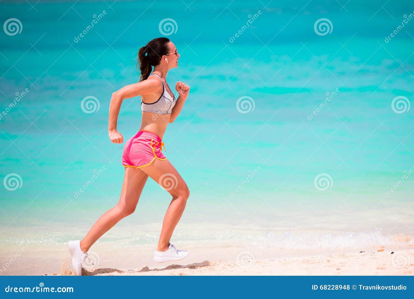 跑沿在她的运动服的热带海滩的适合的少妇
