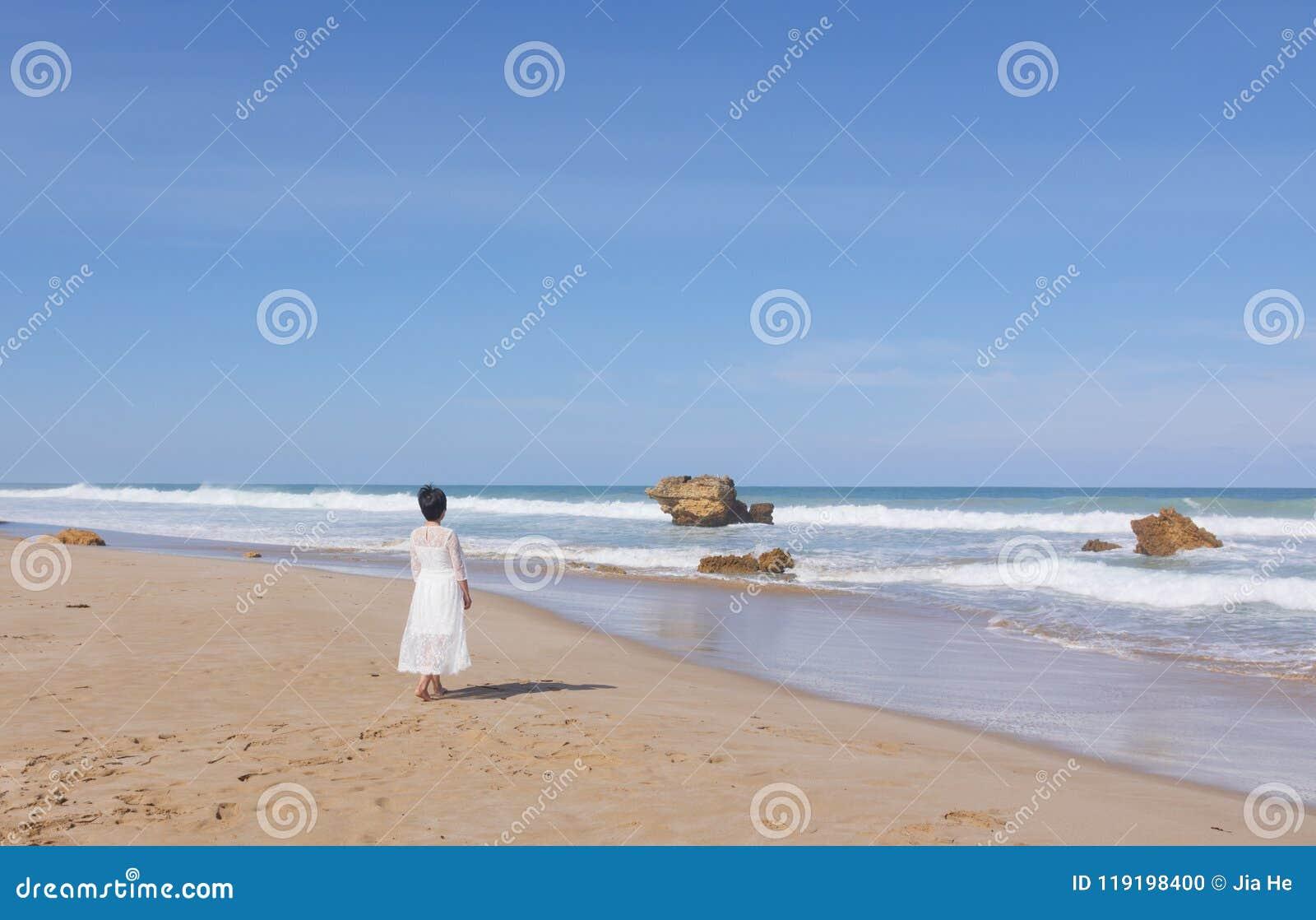 跑沿海滩的婚礼礼服的女孩