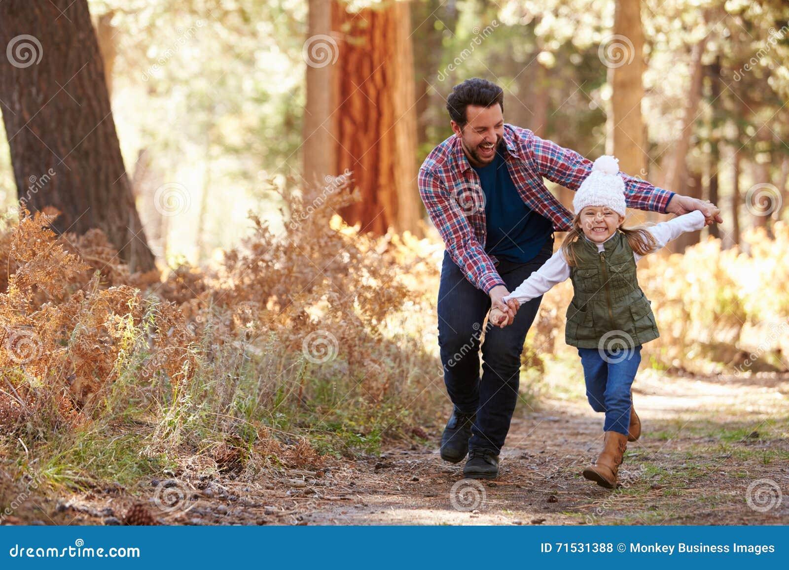 跑通过秋天森林地的父亲和女儿