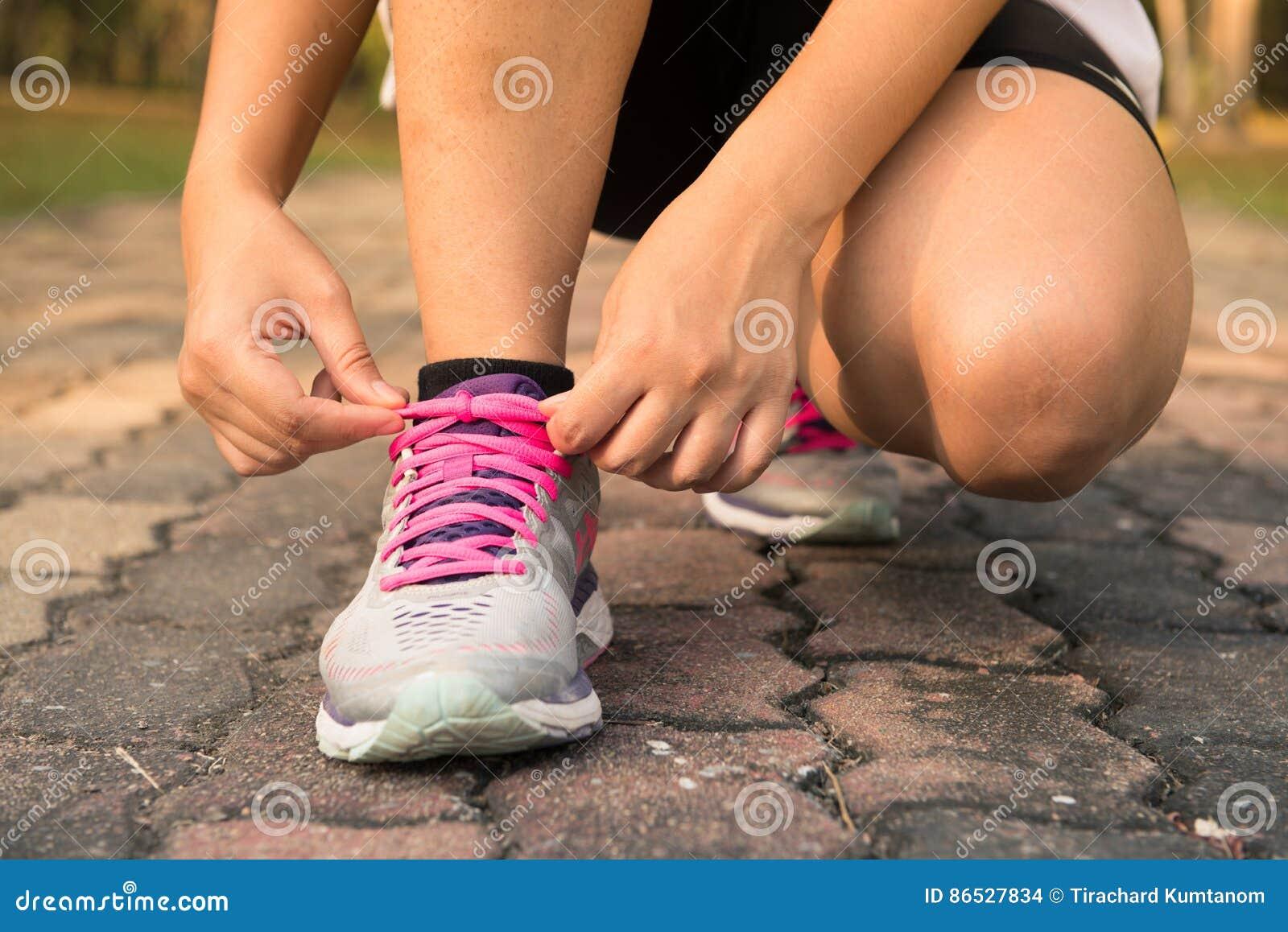 跑鞋-栓鞋带的妇女 准备好母体育健身的赛跑者特写镜头跑步户外在森林