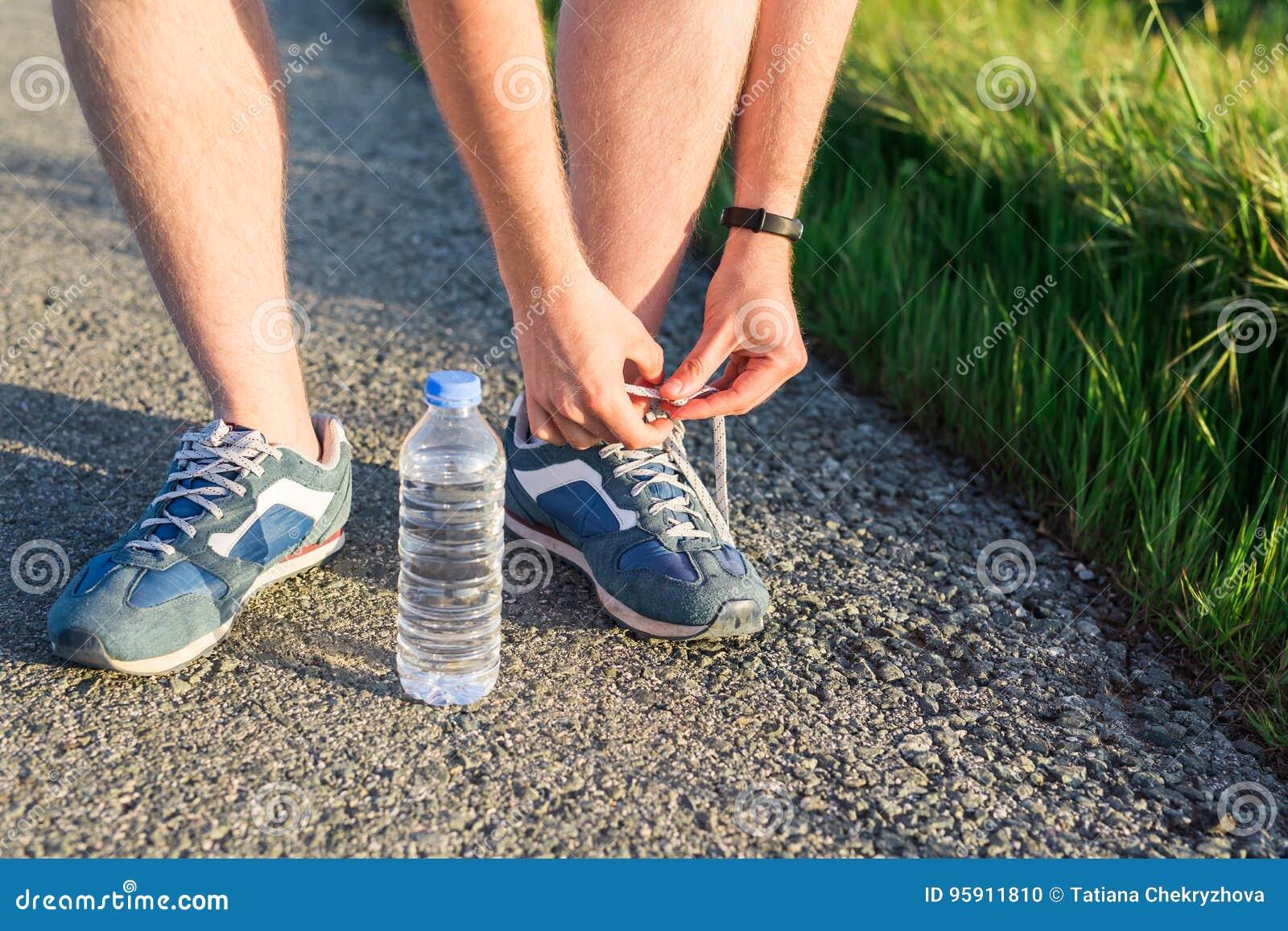 跑鞋 赤足跑鞋关闭  栓跑步的男性运动员鞋带在路 准备好赛跑者的领带