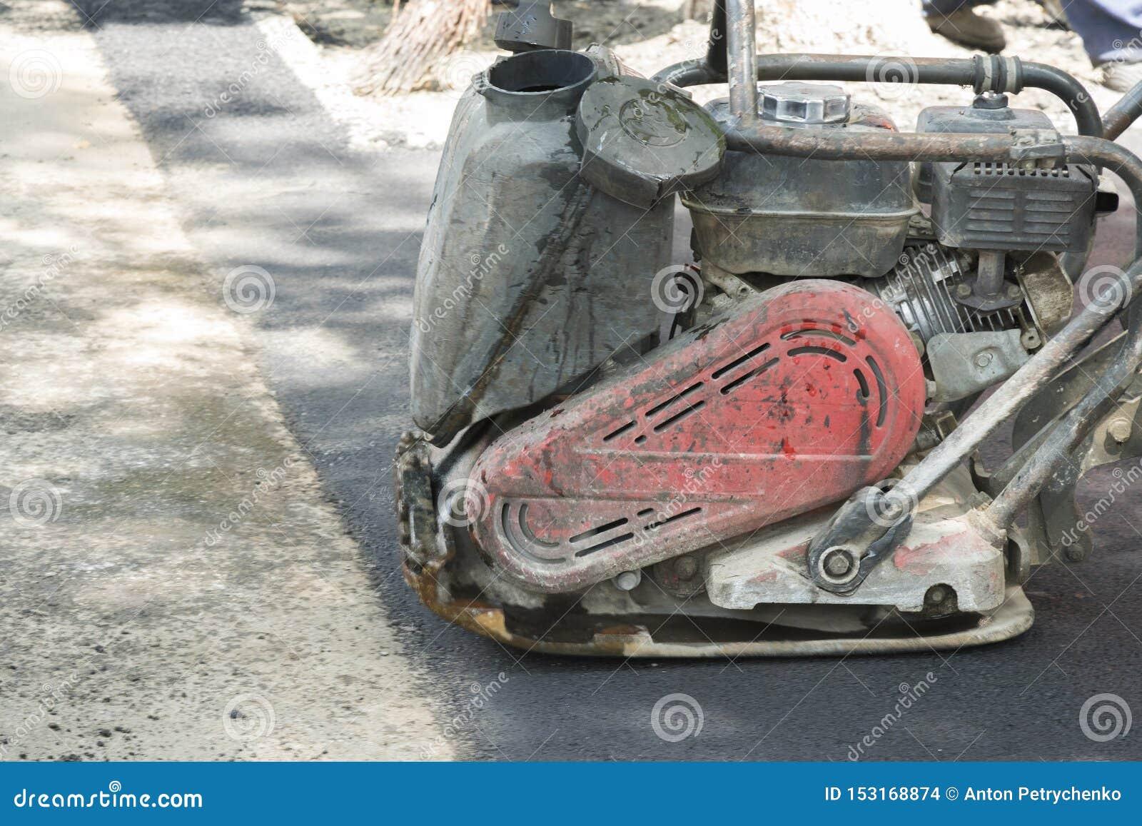 路工作者变紧密与一台振动的拨弹机的沥青在路 有压紧机的工作者在路工地工作