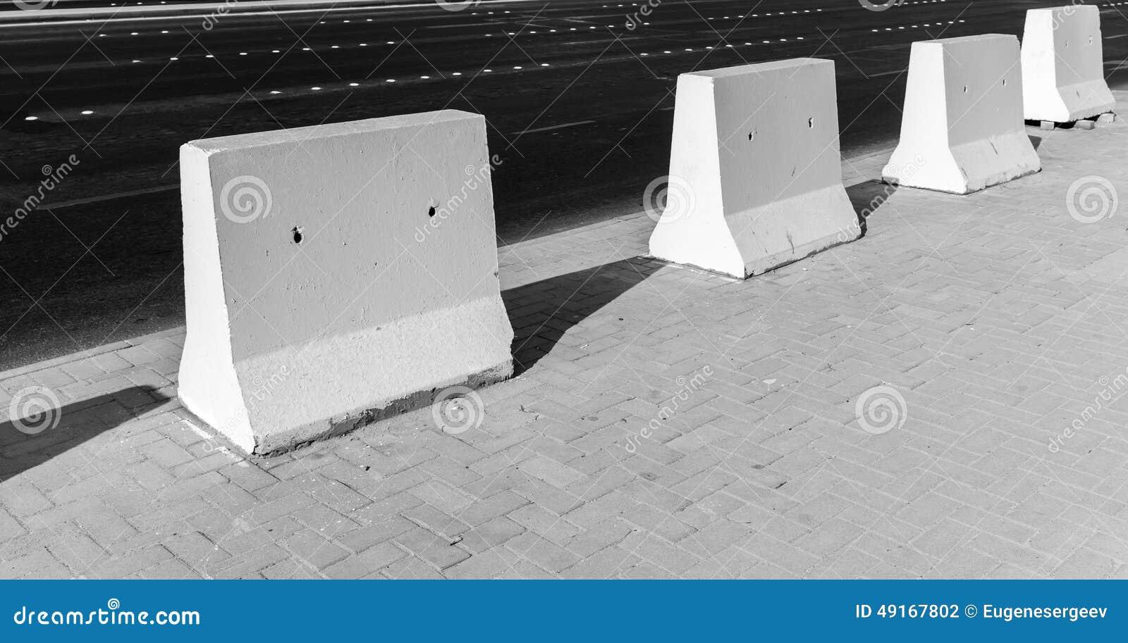 路障碍 在路旁的白色具体块立场
