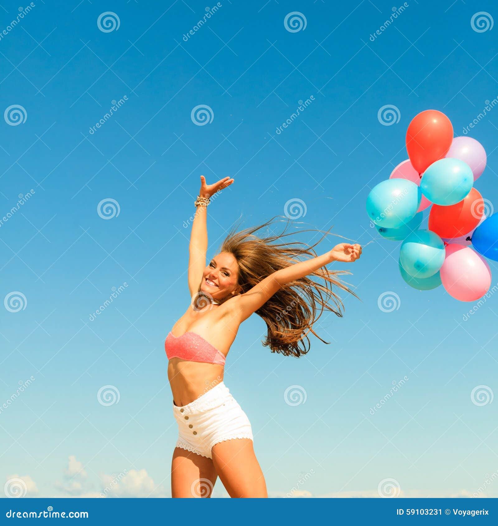 跳与在天空背景的五颜六色的气球的女孩