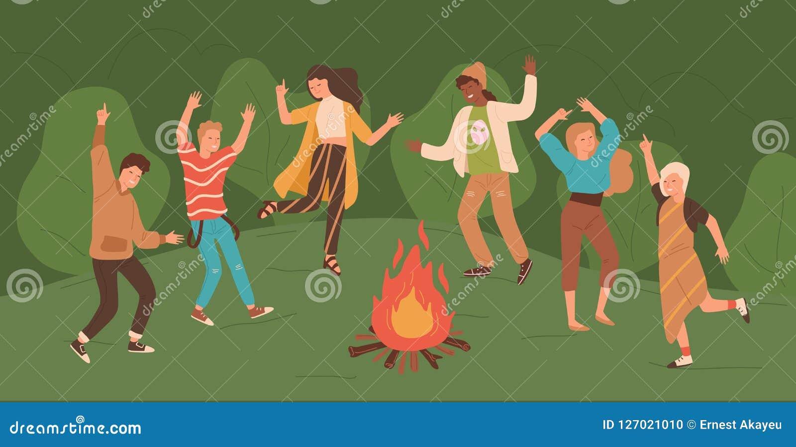 跳舞在享受党的森林人的篝火附近的小组愉快的年轻人和妇女在森林 男和女性