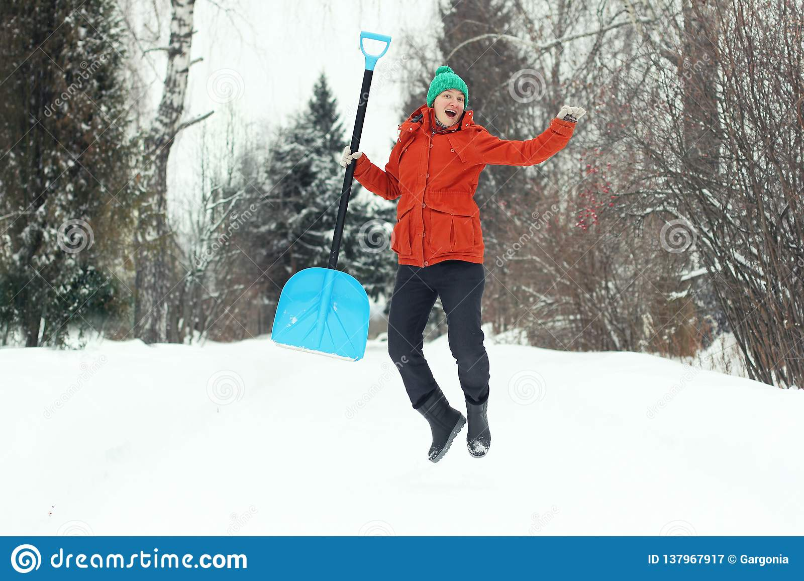 跳跃与在农村路的雪铁锹的滑稽的年轻女人 冬天季节性概念