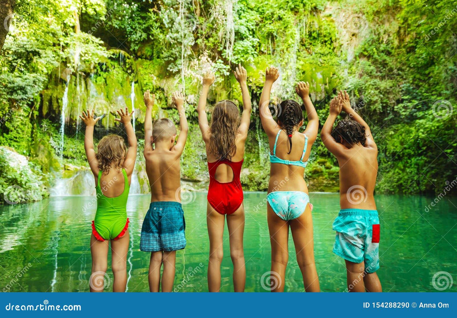 跳跃到湖的愉快的孩子