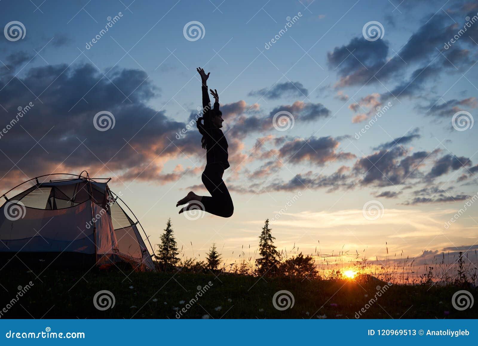 跳跃在与野花的草的愉快的女孩在野营在山在黎明在蓝天下