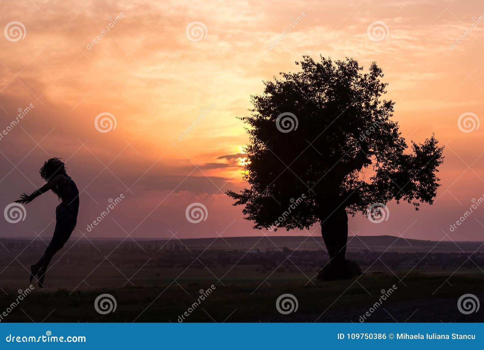 跳跃在日落光的一个美丽的女孩的剪影在树附近
