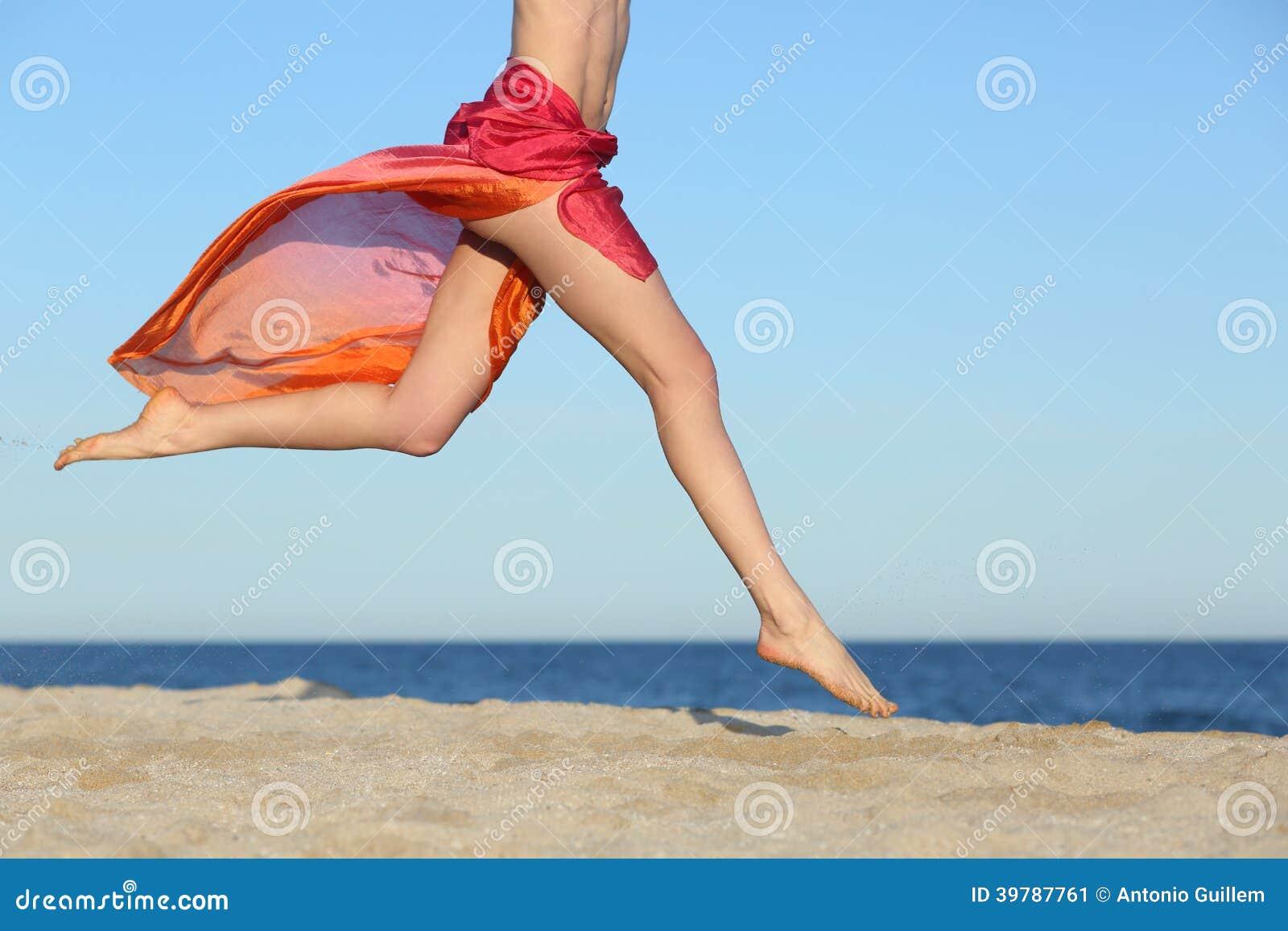 跳跃在海滩的妇女腿愉快