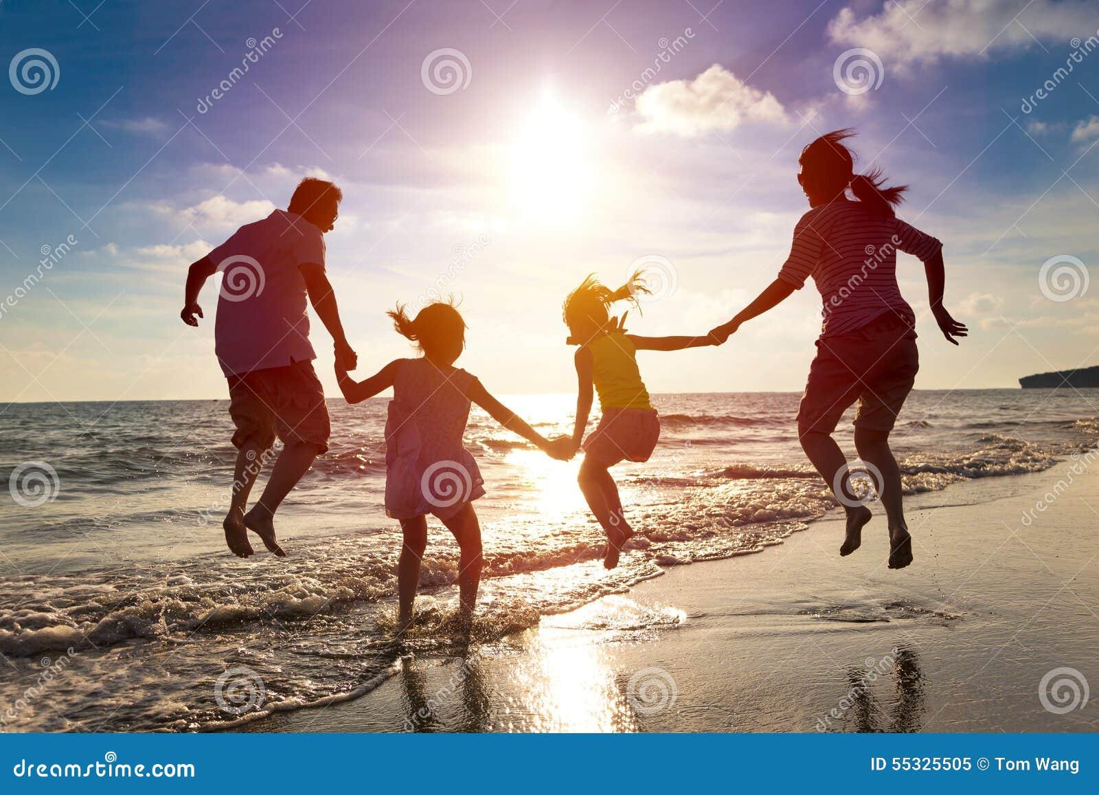 跳跃在海滩的愉快的家庭