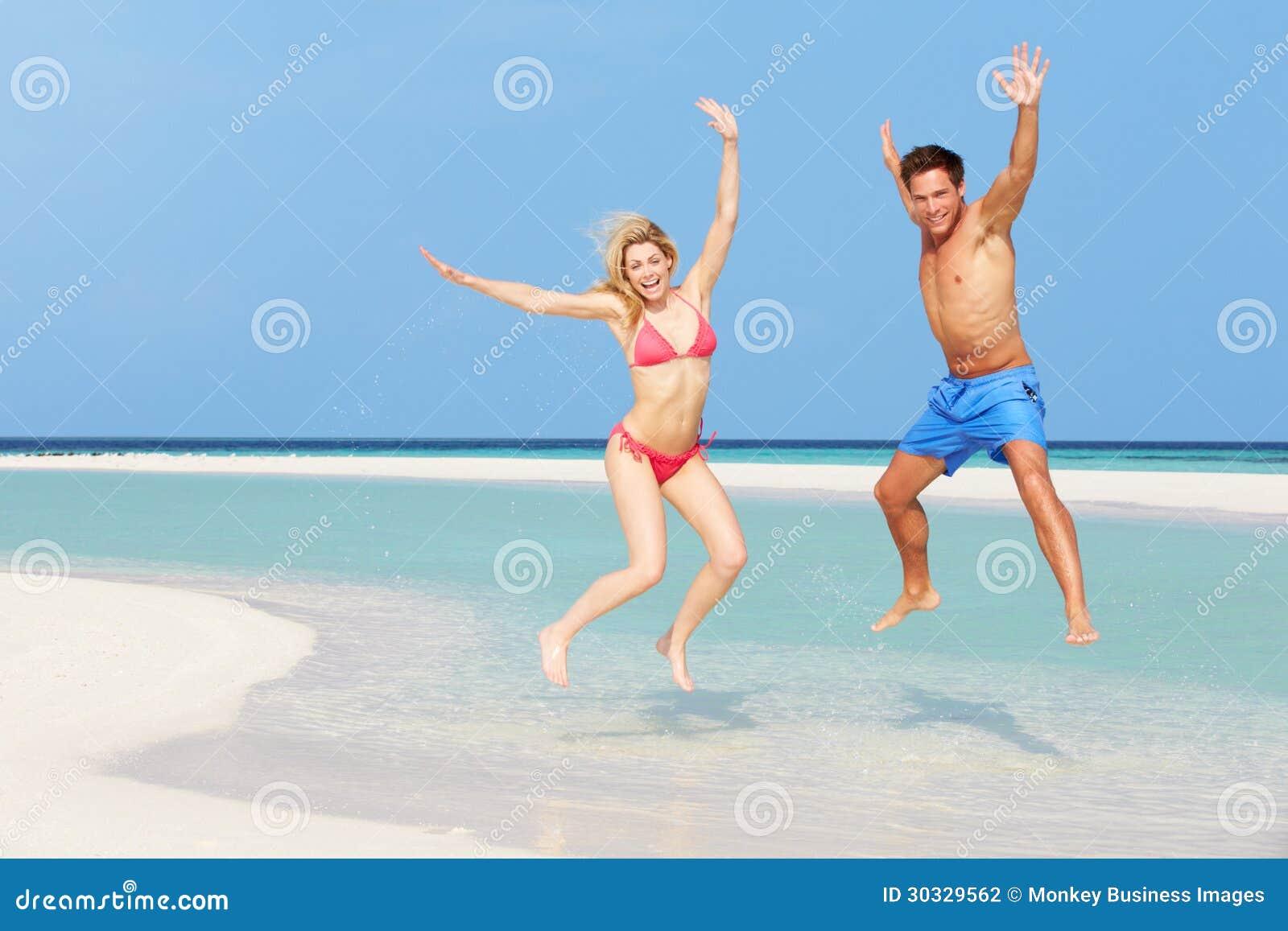跳跃在美丽的热带海滩的夫妇