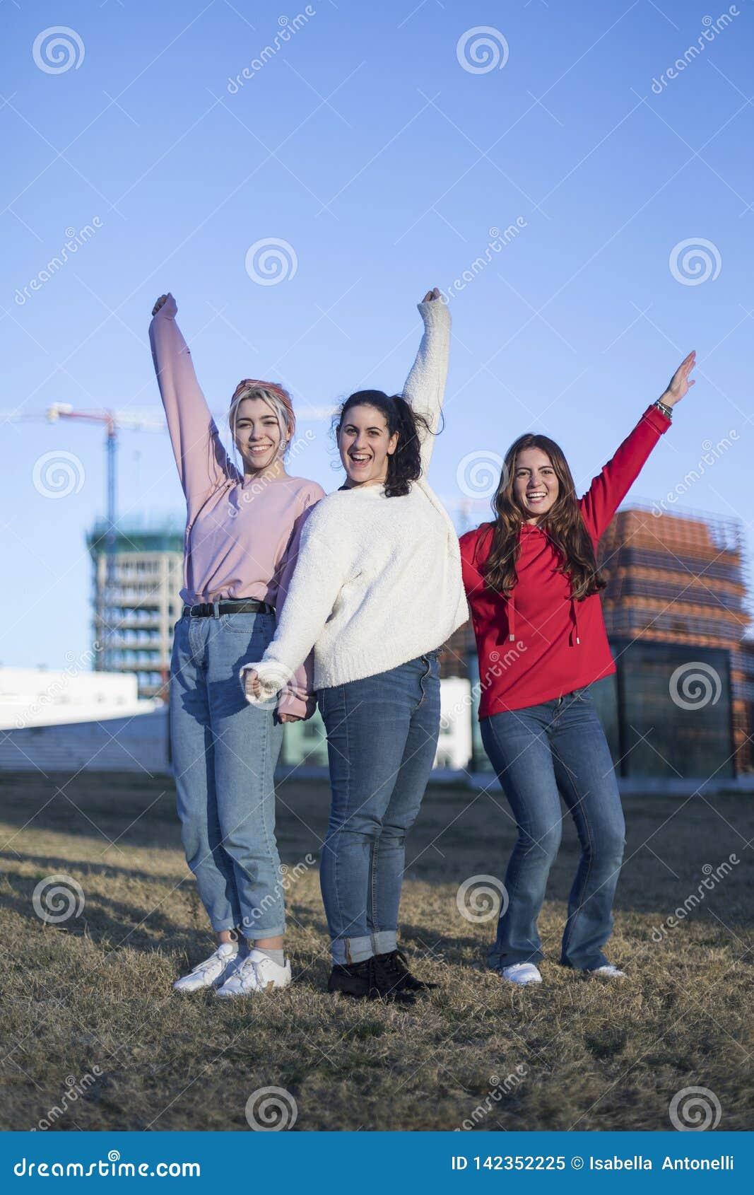 跳跃高在夏天户外背景的天空蔚蓝的三个愉快的青少年的女朋友