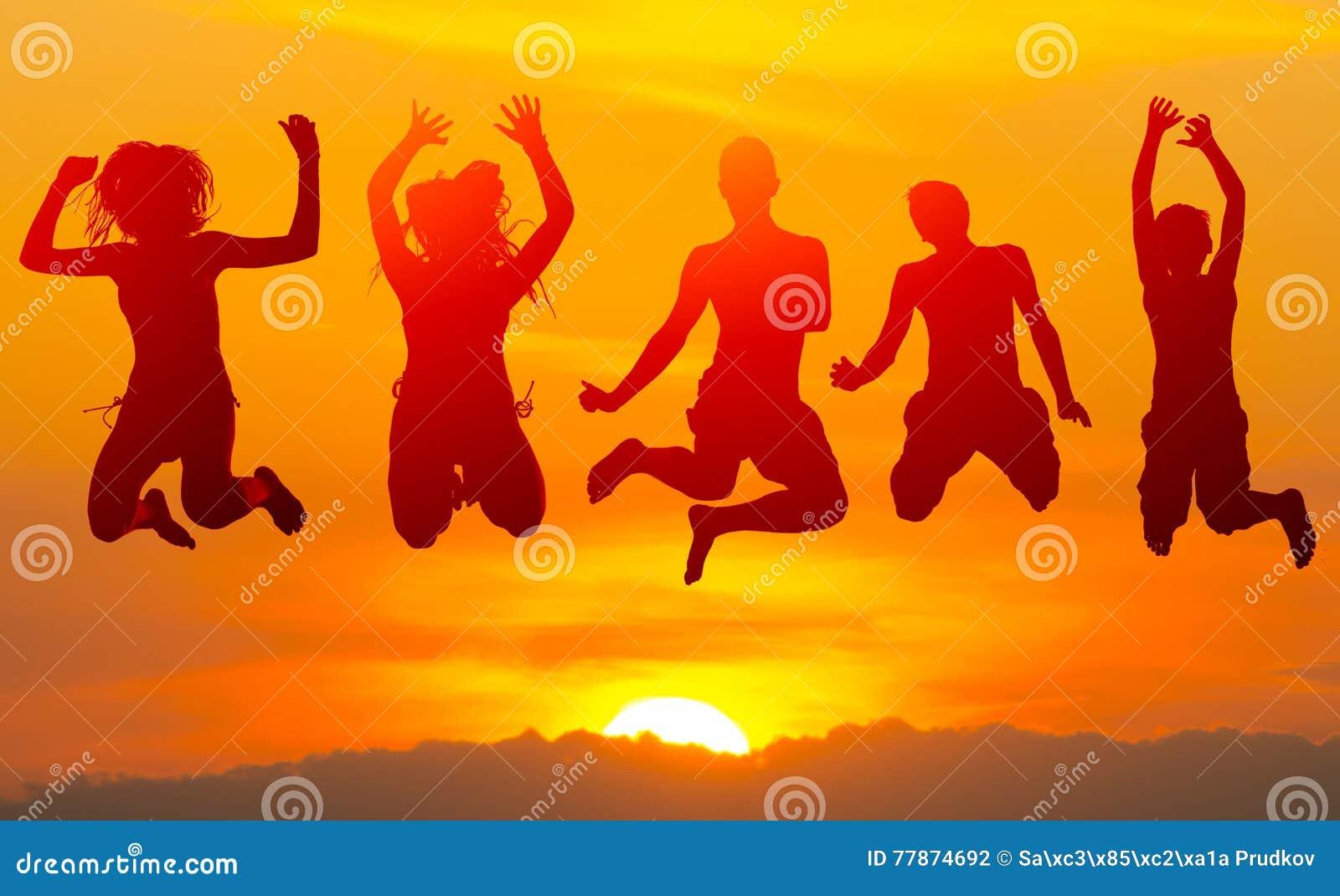 跳跃高在天空中的十几岁的男孩和女孩反对日落