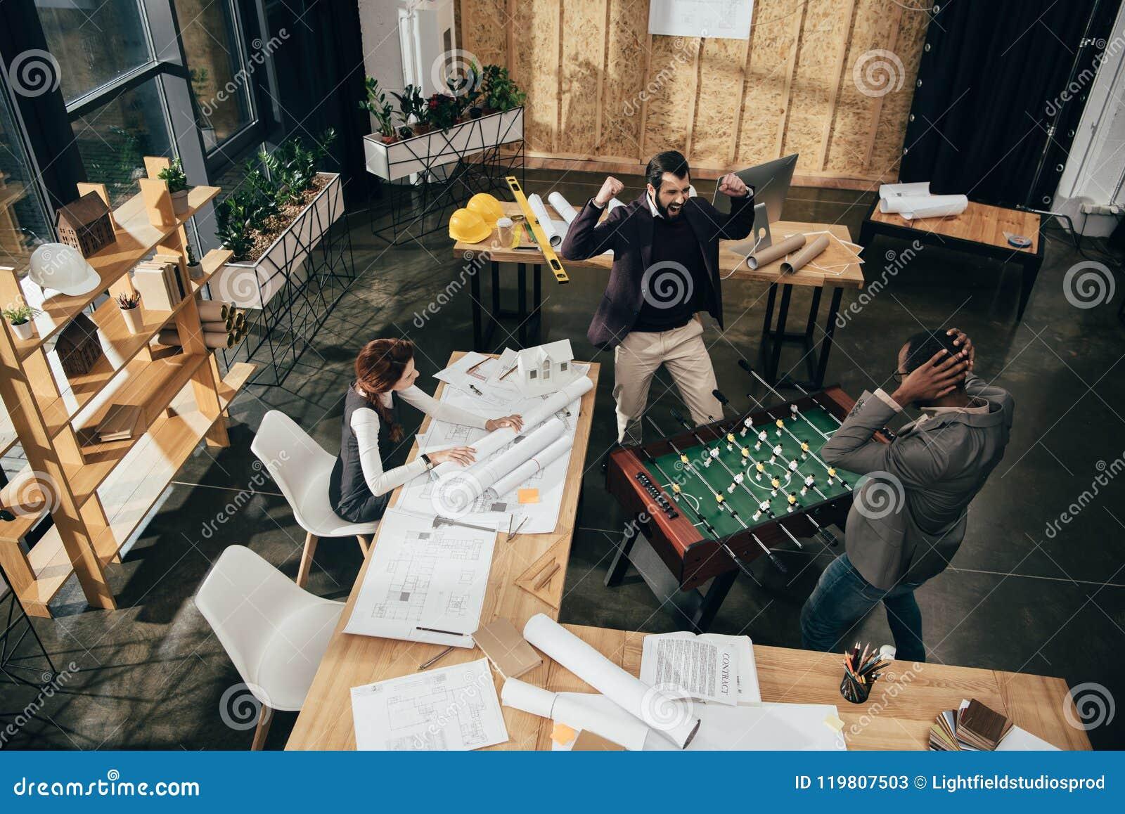 踢桌橄榄球的大角度观点的年轻建筑师