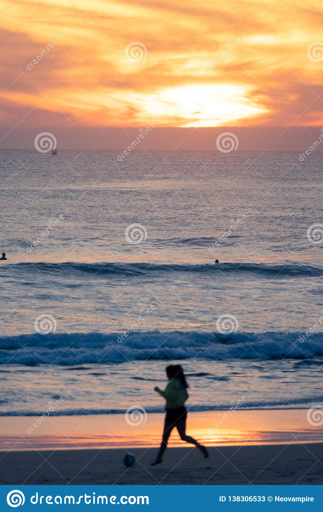 踢足球的女孩在日落,Carcavelos海滩,里斯本,葡萄牙