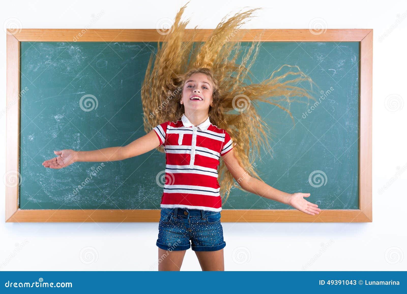 翻转长的头发的滑稽的学生女孩在学校