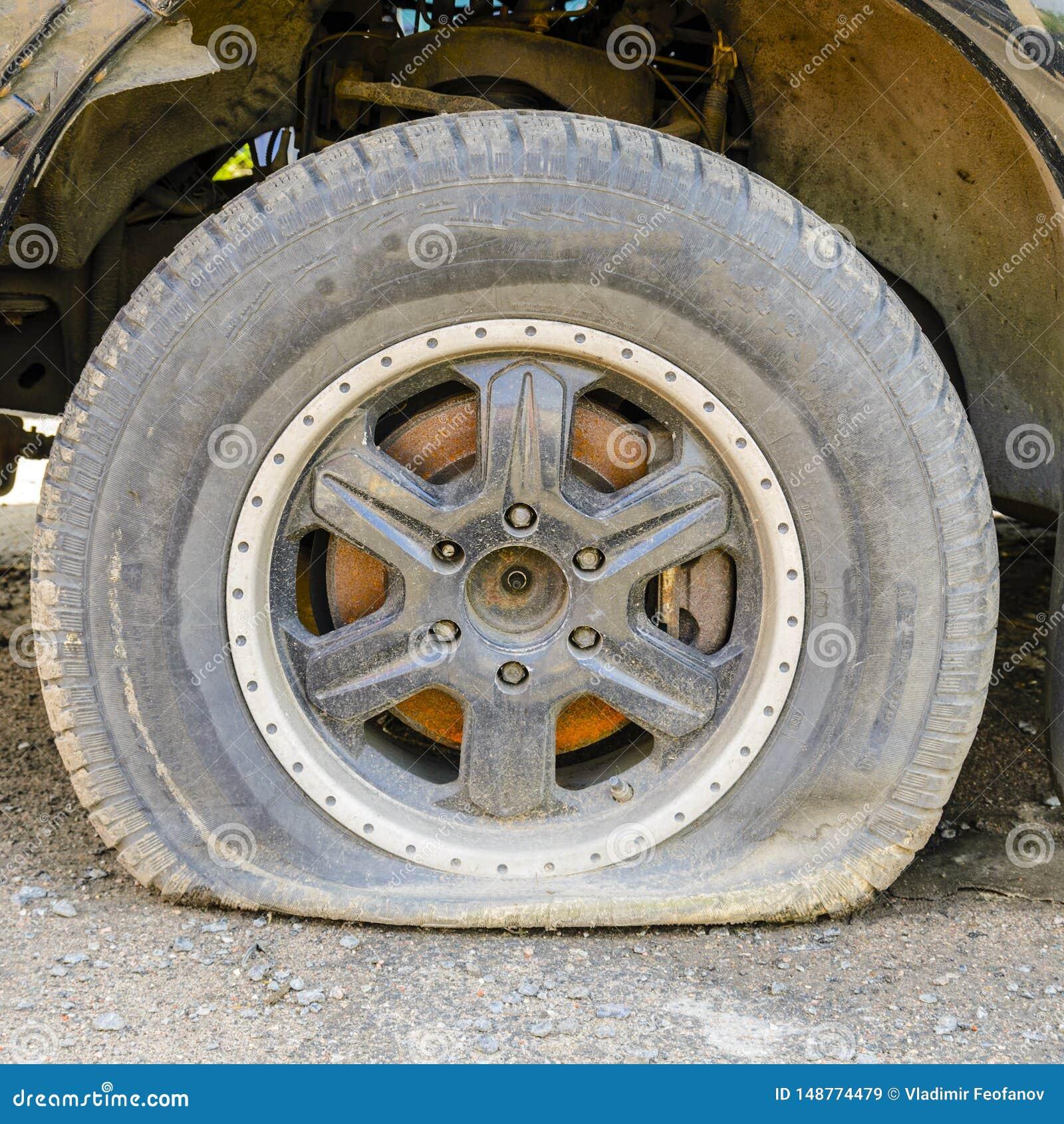 轮子被降下由于汽车、年龄、裁减或者刺轮胎的不活泼 轮胎工作