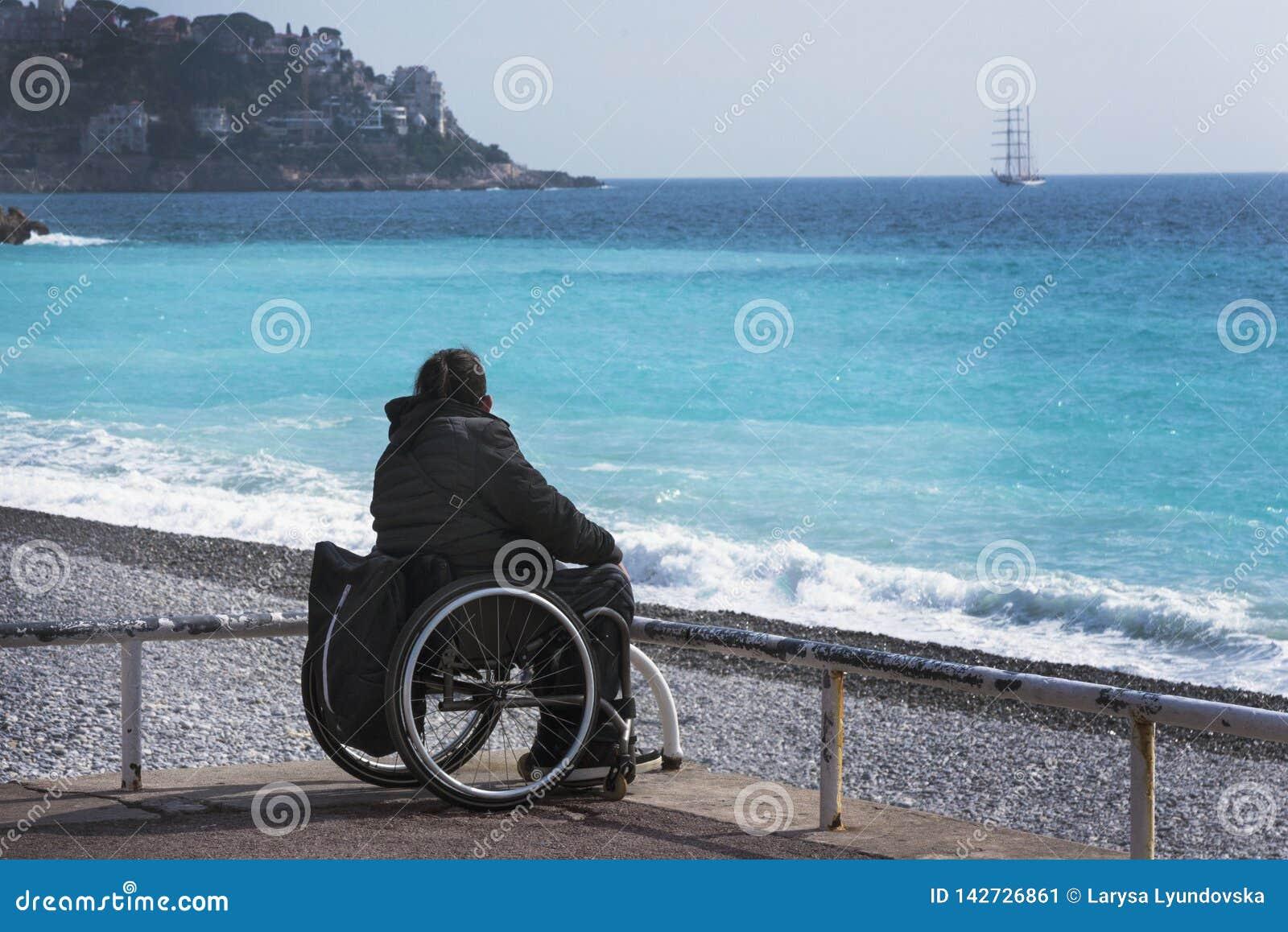 轮椅的一个女孩坐天蓝色的海的岸 美丽的蓝色海、山在阴霾和船在distanc