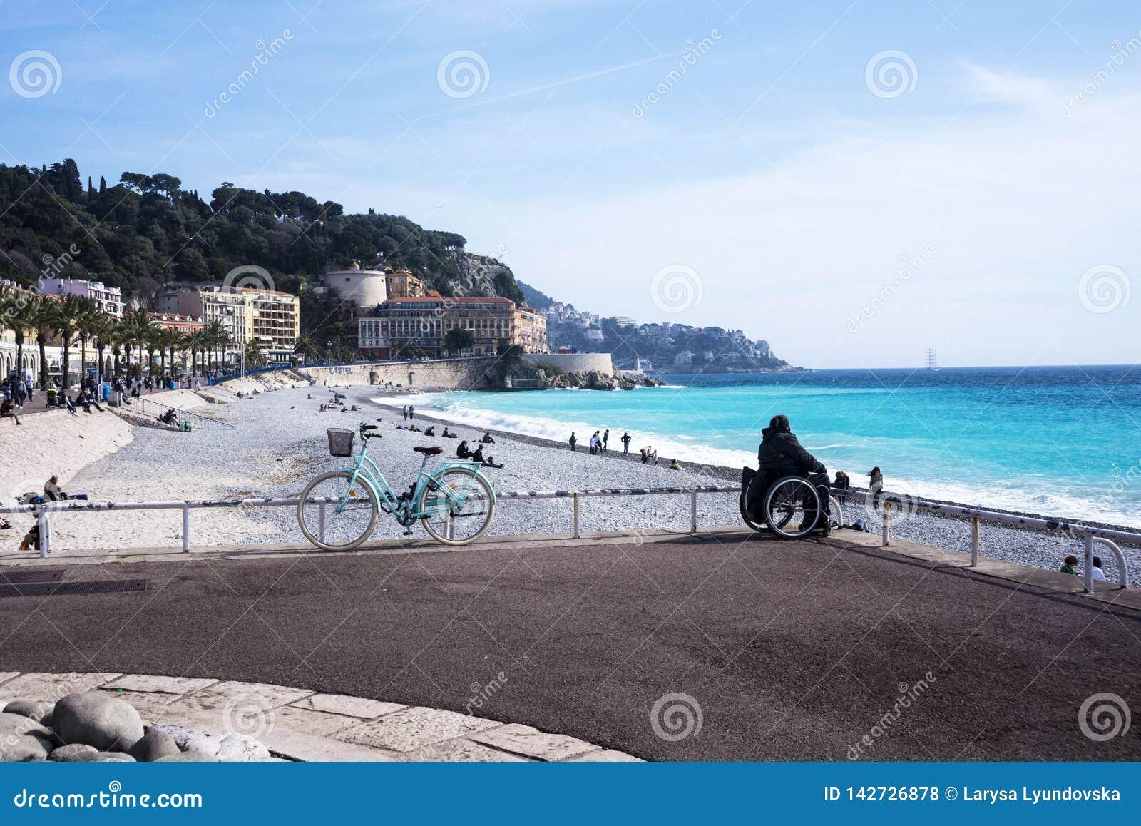 轮椅的女孩坐天蓝色的海的岸 美丽的蓝色海、一辆停放的自行车、山在阴霾和船i