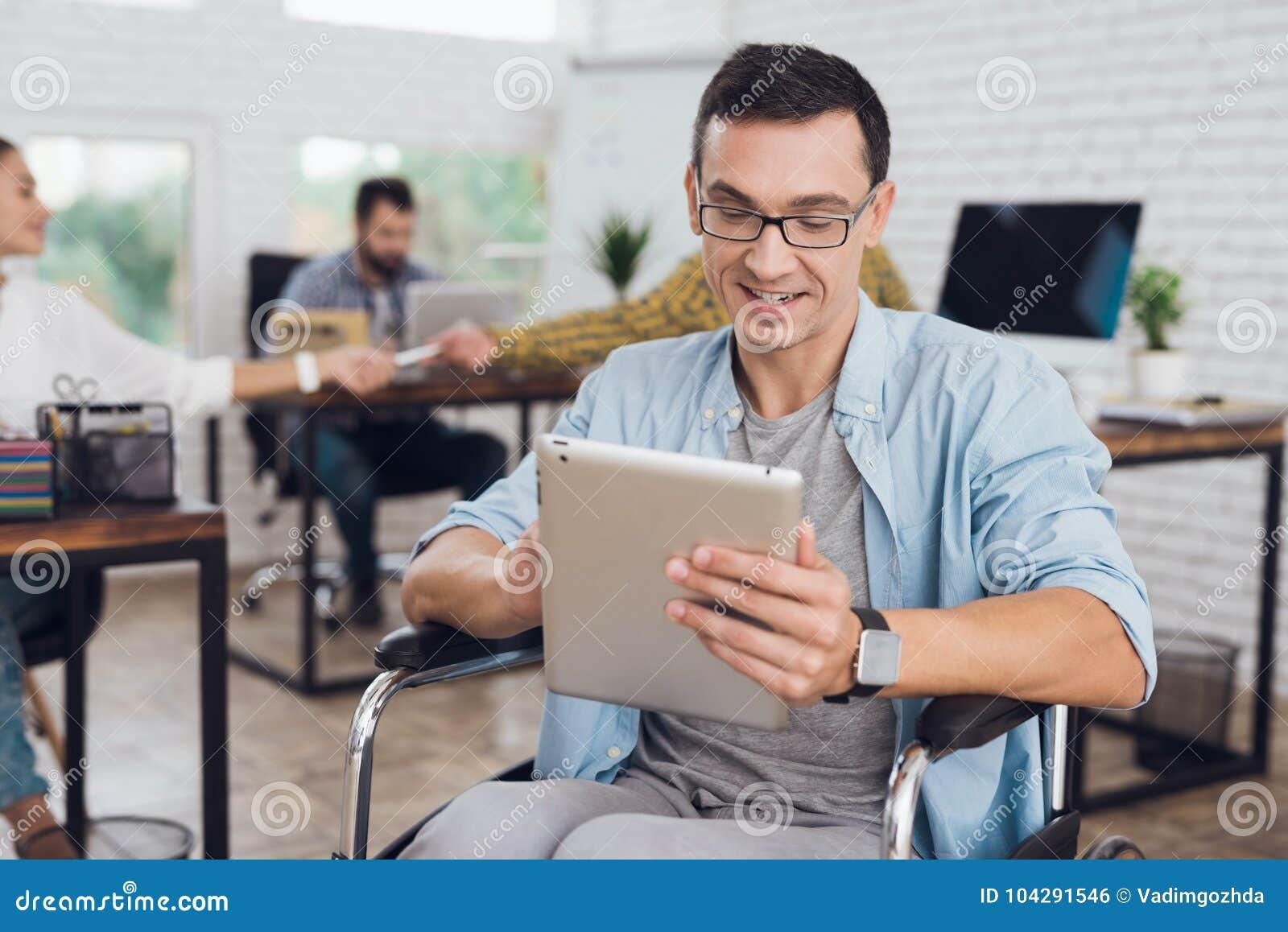 轮椅的残疾人在办公室工作 在他的手上是片剂