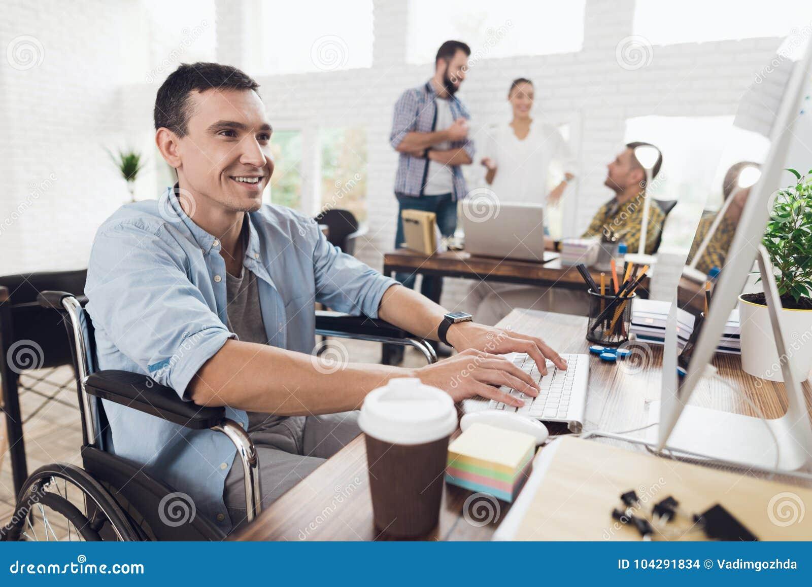 轮椅的残疾人在键盘工作在一张桌上在一个明亮的现代办公室