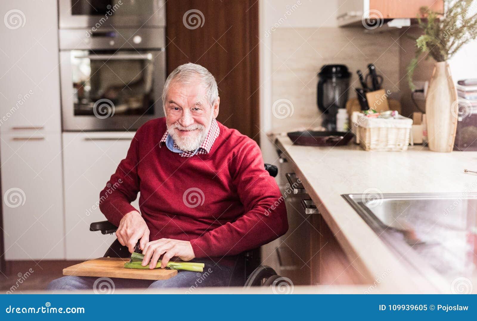 轮椅的老人烹调在厨房里的