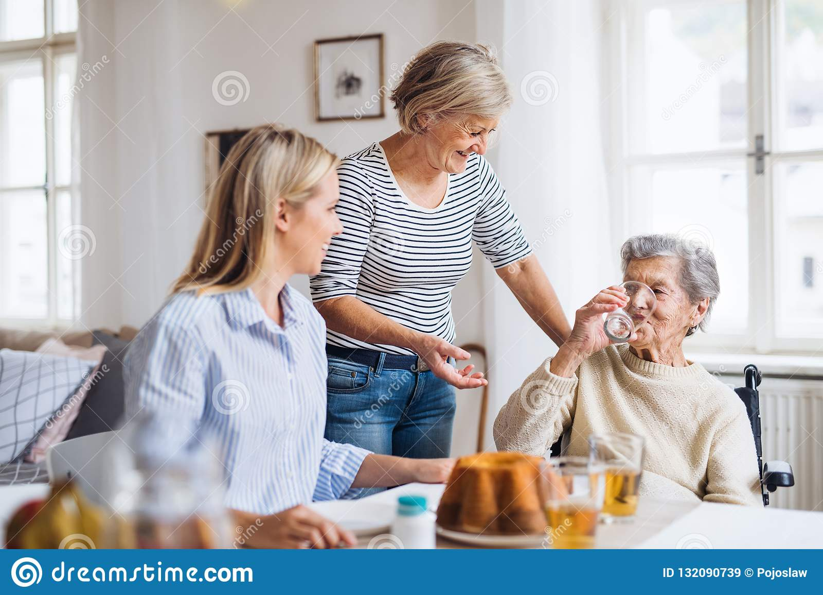 轮椅的资深妇女有在家坐在桌上的家庭的,喝