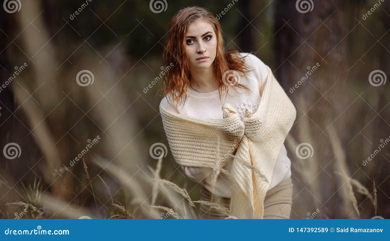轻的衣裳的红发女孩以秋天森林和黄色耳朵为背景