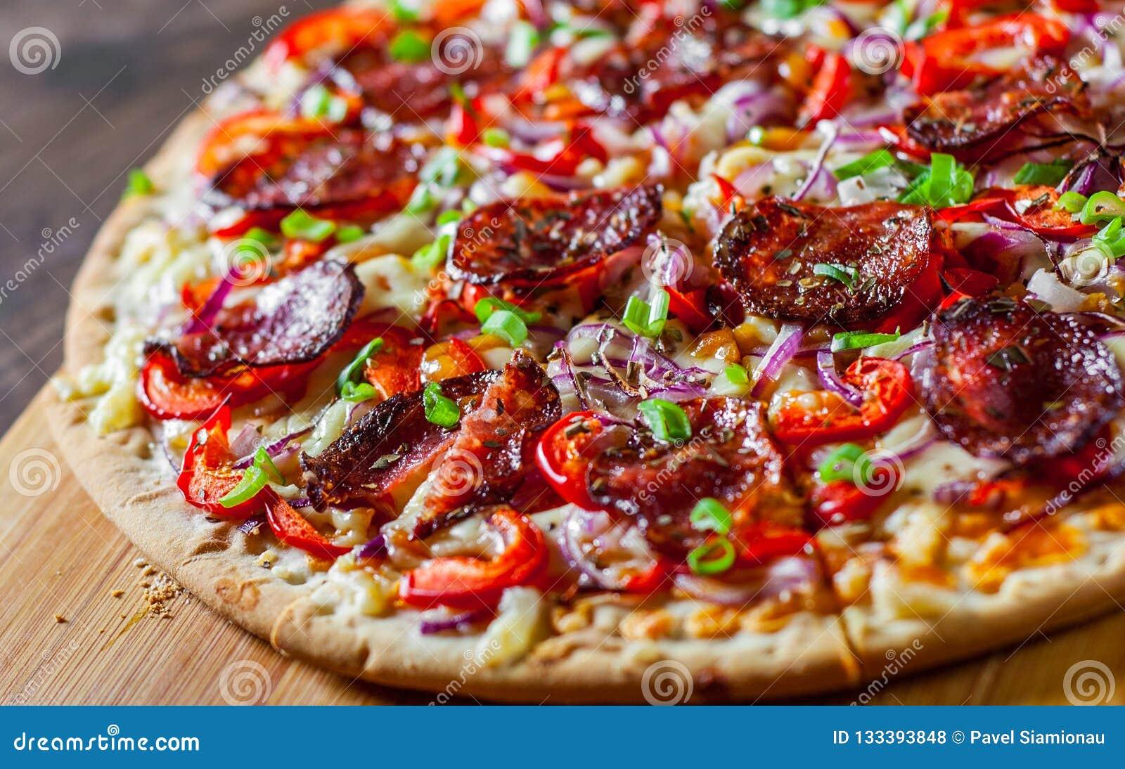 辣香肠烘饼用无盐干酪乳酪,蒜味咸腊肠,西红柿酱,胡椒,葱,加香料 在木桌上的意大利薄饼